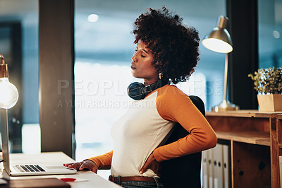 Buy stock photo Cropped shot of an attractive young businesswoman suffering with backache while working at her desk in the office