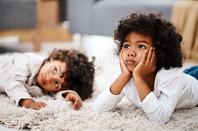 Buy stock photo Cropped shot of two adorable little boys lying down on a carpet and watching tv together at home