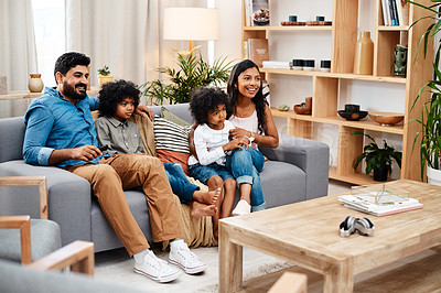 Buy stock photo Full length shot of a beautiful young family sitting on sofa and watching tv together at home