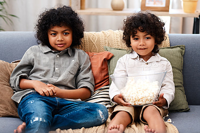 Buy stock photo Cropped shot of two adorable little boys eating popcorn and watching movies together at home