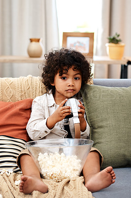 Buy stock photo Full length shot of an adorable little boy eating popcorn and listening to music on headphones at home