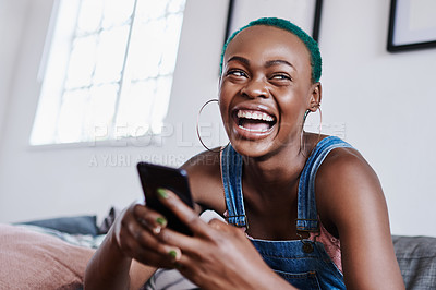 Buy stock photo Shot of a young woman using a cellphone while relaxing at home