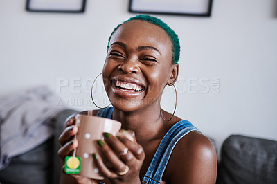 Buy stock photo Shot of a young woman drinking tea while relaxing at home