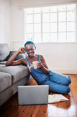 Buy stock photo Shot of a young woman drinking tea while using a laptop at home