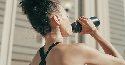 Buy stock photo Rearview shot of a sporty young woman drinking water while exercising in the city