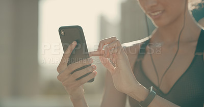 Buy stock photo Closeup shot of a sporty woman using a cellphone in the city