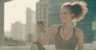 Buy stock photo Shot of a sporty young woman using a cellphone in the city