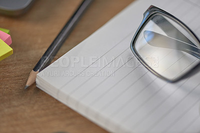 Buy stock photo Still life shot of a pencil, a pair of glasses and a note pad on a wooden table