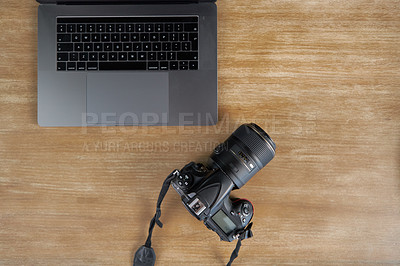 Buy stock photo High angle shot of a laptop and camera on a wooden table