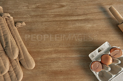 Buy stock photo High angle shot of a pair of oven mitts and broken egg shells on a kitchen counter top after baking