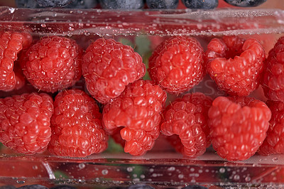 Buy stock photo High angle shot of a punnet of raspberries on a counter top in an empty kitchen