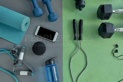 Buy stock photo High angle shot of a variety of workout equipment laid out on a green exercise mat before a workout