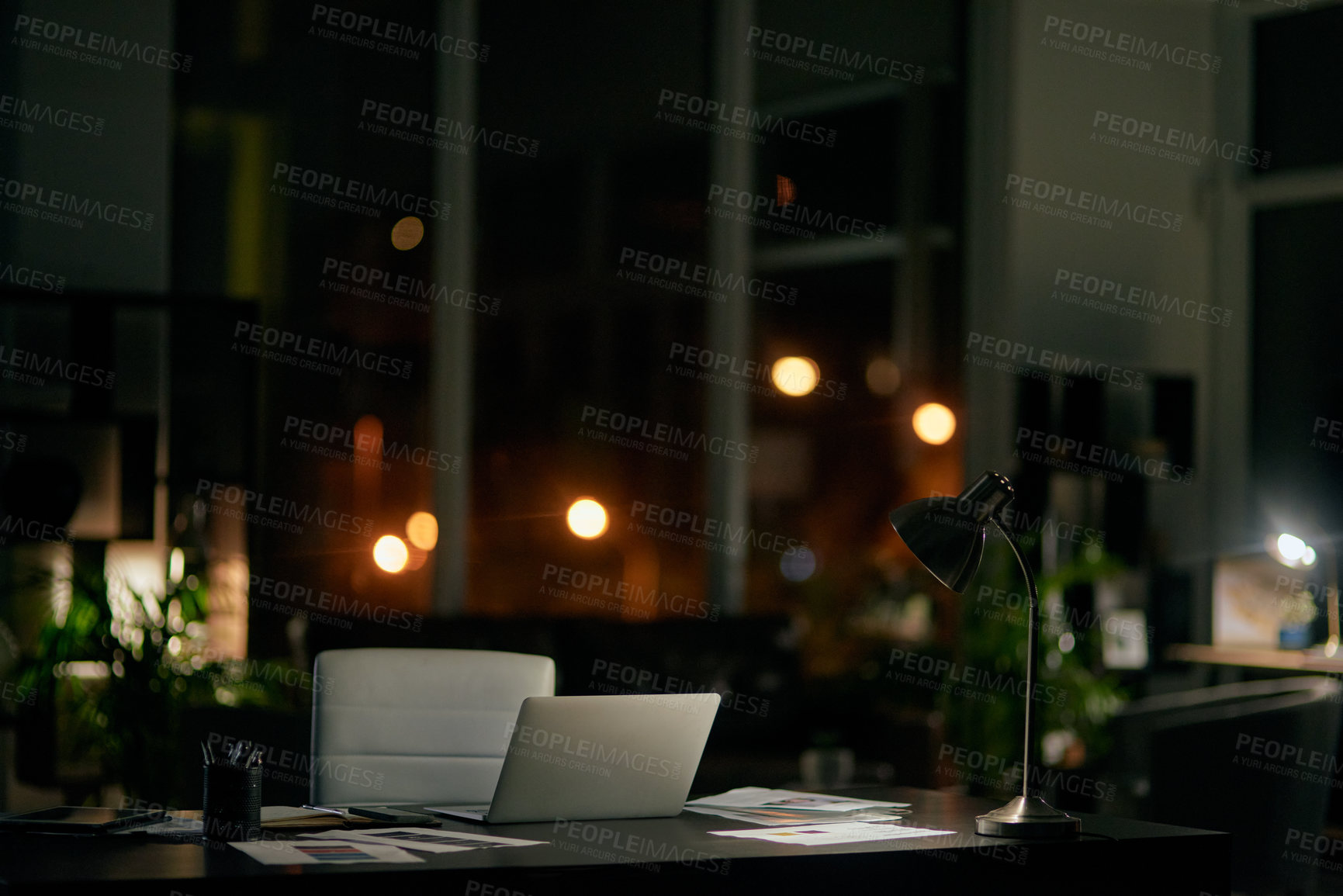 Buy stock photo Cropped shot of a businessperson's workspace in an empty office during a late shift