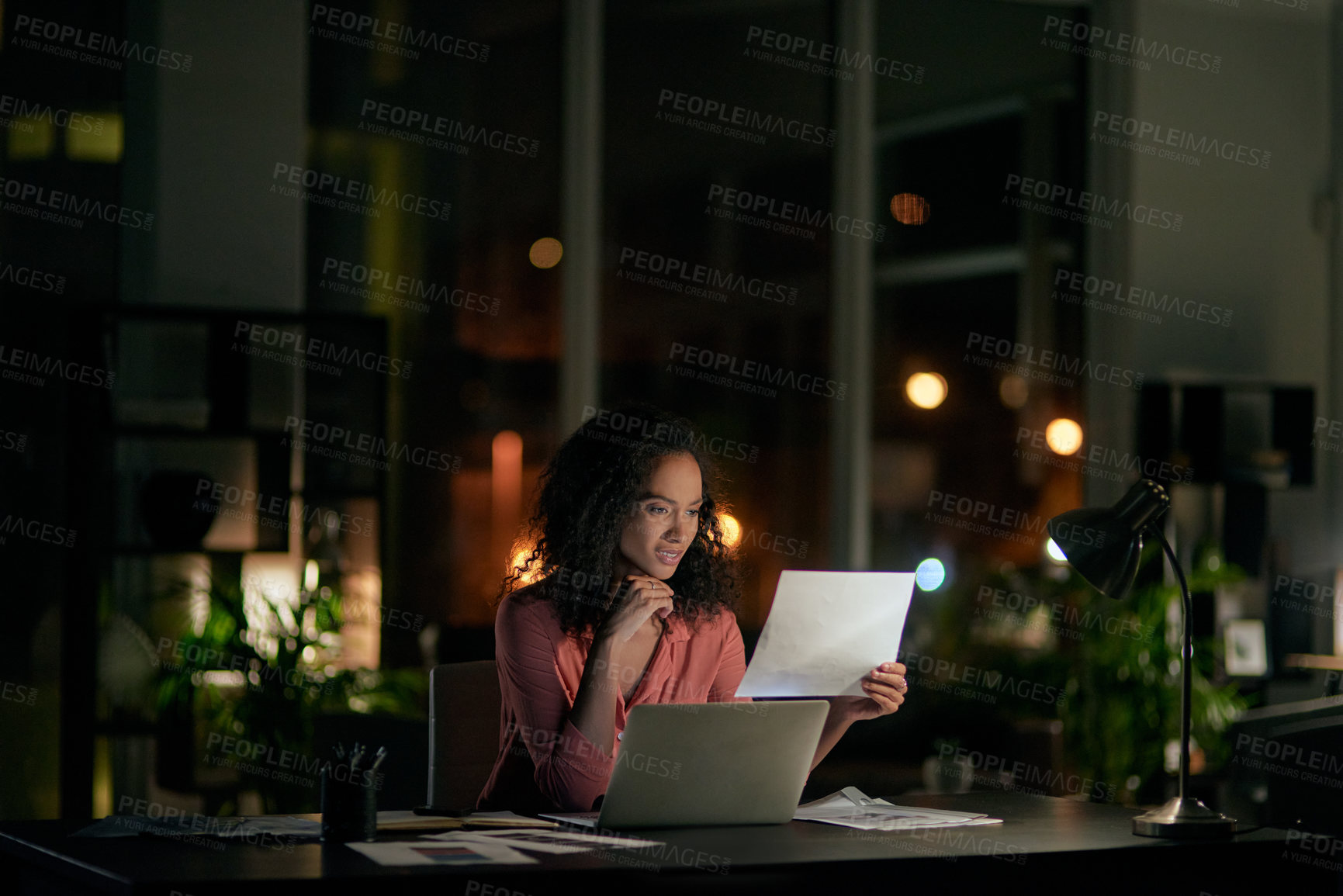 Buy stock photo Cropped shot of an attractive young businesswoman sitting alone in the office and feeling confused while reading paperwork at night