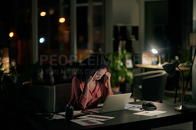Buy stock photo Cropped shot of an attractive young businesswoman sitting and feeling stressed during a late shift in the office