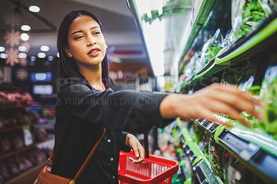 Buy stock photo Shot of a young woman shopping for fresh vegetables in a grocery store