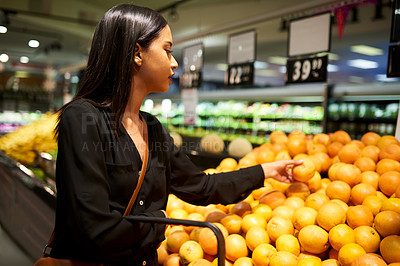 Buy stock photo Shot of a young woman shopping for oranges in a grocery store