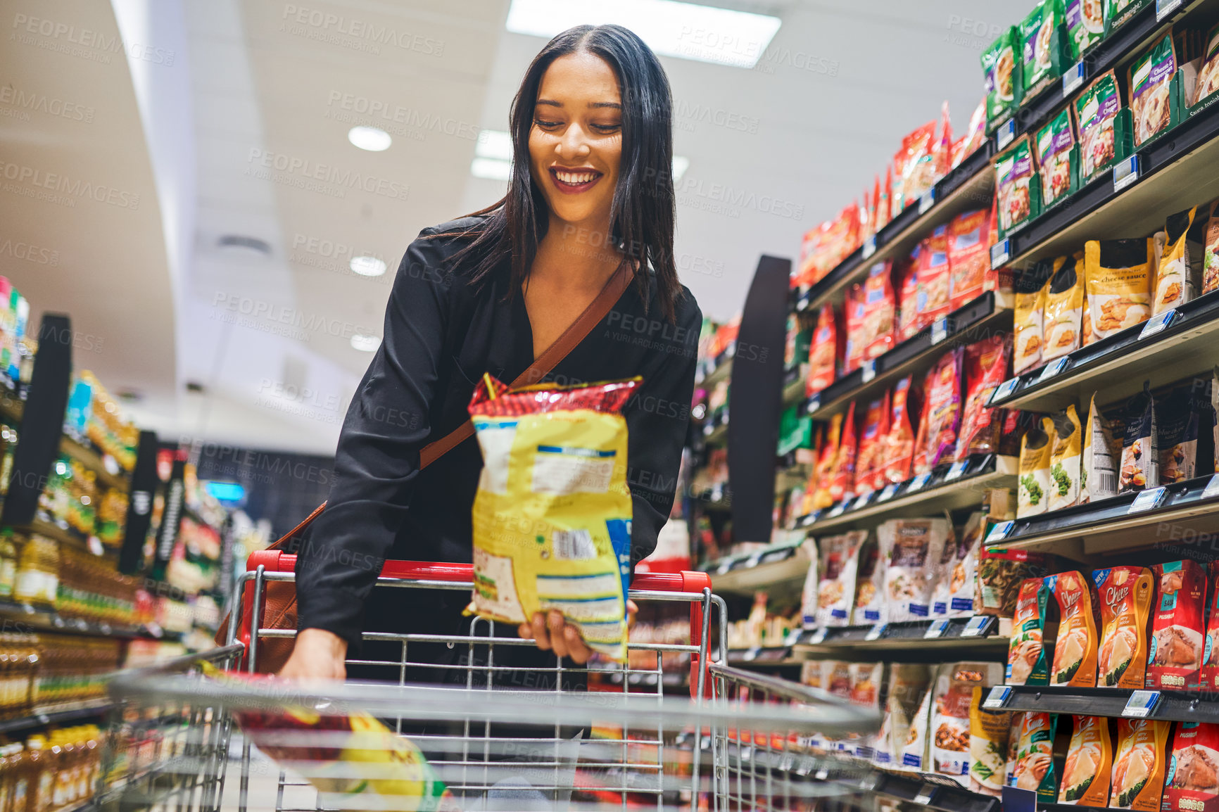 Buy stock photo Shot of a young woman shopping in a grocery store