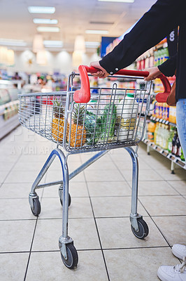 Buy stock photo Cropped shot of a woman pushing a shopping cart in a grocery store