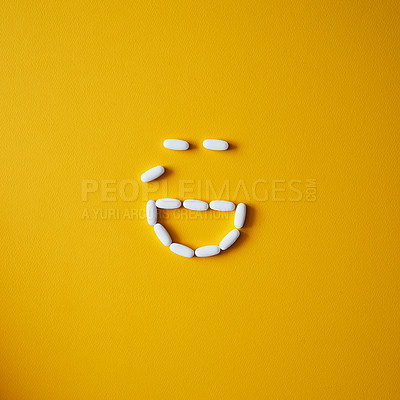 Buy stock photo Studio shot of tablets arranged in the shape of a crying face against a mustard background