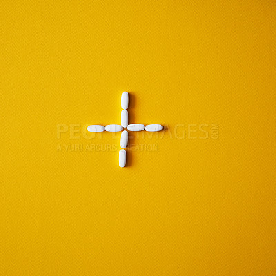 Buy stock photo Studio shot of  tablets arranged in the shape of a plus sign against a mustard background