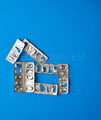 Buy stock photo Studio shot of a bunch of empty pill blister packs against a blue background