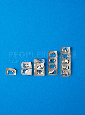 Buy stock photo Studio shot of empty blister packs arranged in an increasing order of size against a blue background