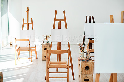 Buy stock photo Cropped shot of a group of easels and blank canvases in an empty art studio before a painting class