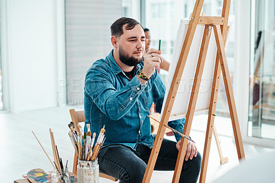 Buy stock photo Cropped shot of a handsome young artist sitting and painting during an art class in the studio