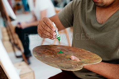 Buy stock photo Cropped shot of an unrecognizable artist squeezing paint onto a palette during an art class in the studio