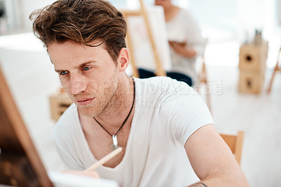 Buy stock photo Cropped shot of a handsome young artist sitting and looking contemplative during an art class in the studio