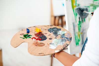 Buy stock photo Cropped shot of an unrecognizable artist standing and painting on a canvas during a painting session in an art studio