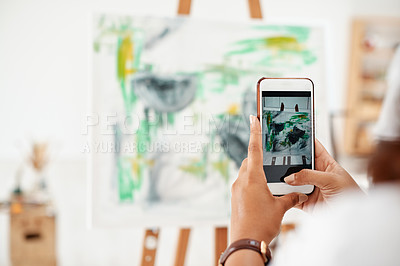 Buy stock photo Cropped shot of an unrecognizable artist standing and taking a picture of her artwork with her cellphone in the studio