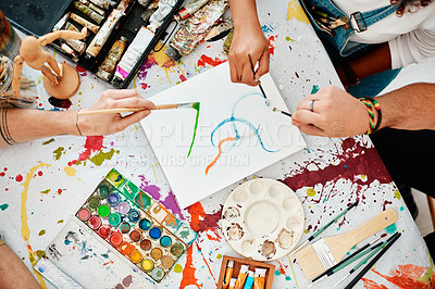 Buy stock photo High angle shot of an unrecognizable group of artists sitting together and painting during an art class in the studio