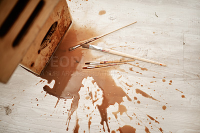 Buy stock photo High angle shot of spilled coffee and paintbrushes on the floor after an art class in an empty studio