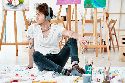 Buy stock photo Full length shot of a handsome young artist sitting alone and looking contemplative while listening to music through headphones