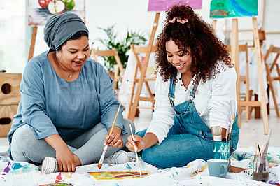 Buy stock photo Full length shot of two attractive young artists sitting together and painting during an art class in the studio