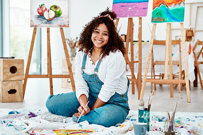 Buy stock photo Full length portrait of an attractive young artist sitting alone and painting during an art class in the studio