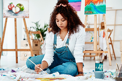 Buy stock photo Full length shot of an attractive young artist sitting alone and painting during an art class in the studio