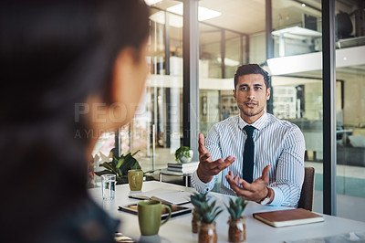 Buy stock photo Cropped shot of a young businessman sitting in a meeting in the boardroom