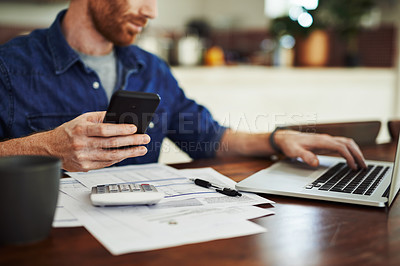 Buy stock photo Closeup shot of an unrecognisable man using a cellphone and laptop while going through paperwork at home