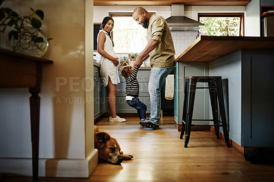 Buy stock photo Shot of a young family spending quality time in the kitchen at home
