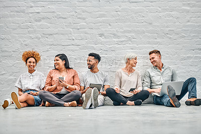 Buy stock photo Full length shot of a diverse group of businesspeople sitting together and using technology in the office during the day