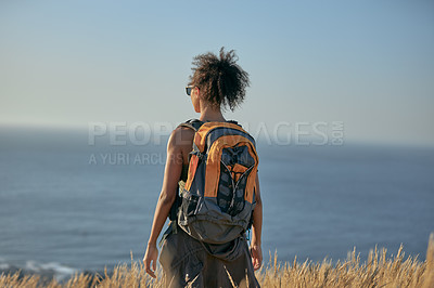 Buy stock photo Rearview shot of a young woman hiking out in the mountains on a sunny day