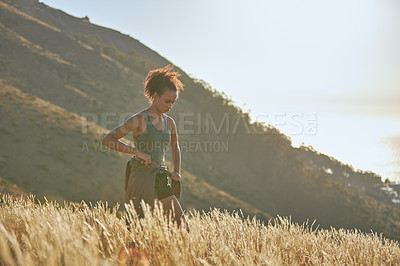 Buy stock photo Shot of an attractive young woman tying her shirt around her waits while hiking through the mountains outdoors