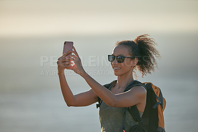 Buy stock photo Shot of an attractive young woman taking selfies with her cellphone while hiking outdoors in the mountains