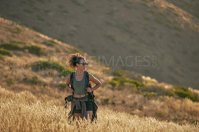 Buy stock photo Shot of an attractive young woman hiking out in the mountains on a sunny day