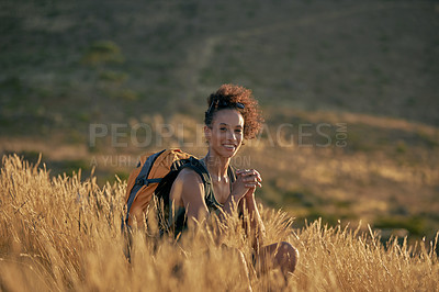 Buy stock photo Portrait of an attractive young woman taking a break while hiking out in the mountains on a sunny day