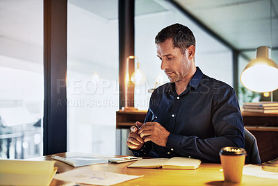 Buy stock photo Shot of a mature businessman using a smartphone during a late night in a modern office