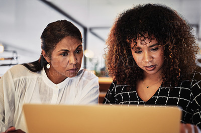 Buy stock photo Shot of two businesswomen using a laptop during a late night in a modern office
